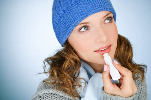 Young woman applying lip balm, in wintertime